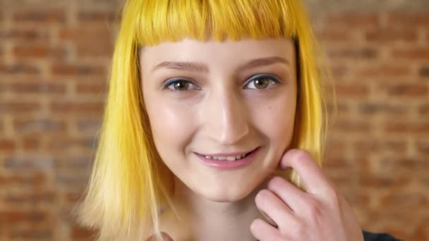 Modern youth, young woman with yellow hair smiling at camera, beauty portrait, brick background