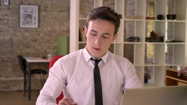 Mladý podnikatel pracuje s notebookem a pití kávy v kanceláři, sleduje kamera, obchodní koncept, komunikační koncept