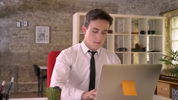 Young businessman is working with laptop in office, watching at camera, business concept, communication concept