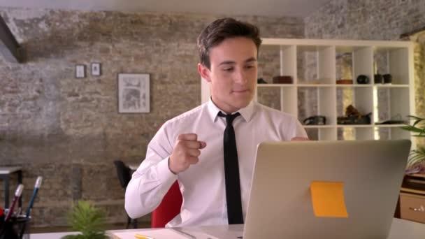 Mladý podnikatel pracuje s přenosným počítačem v kanceláři, šťastný kvůli dobré zprávy, vedení ruky pěst, gesto koncepce, obchodní koncept, komunikační koncept