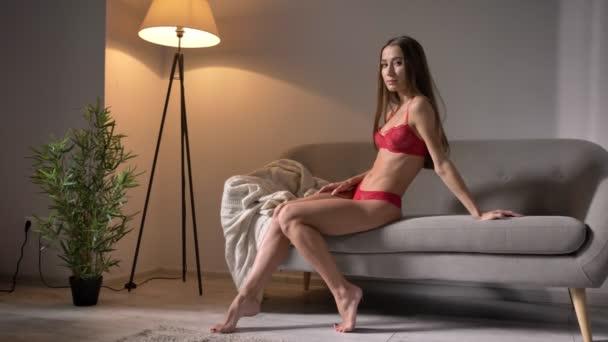 Mladá atraktivní žena v červené spodní prádlo, sedí na gauči a při pohledu na fotoaparát, dokonalé tělo cíl
