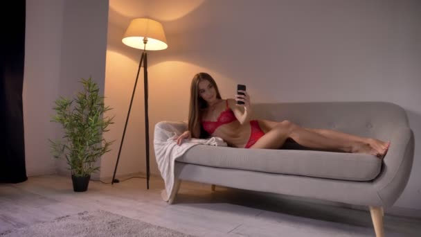 Young sexy woman in red lingerie taking selfie and lying on couch in living room, beautiful perfect body, attractive and seductive