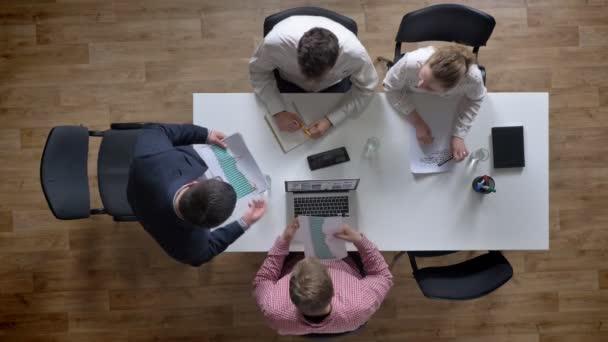 Chef kommt herein und gibt jedem Dokument, Topshot, Geschäftsteam hält Besprechung in modernem Büro ab, Sitzungssaal über Kopf