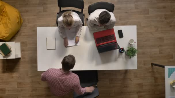 Male candidate for job is interviewed by two employers, topshot, sitting in modern office
