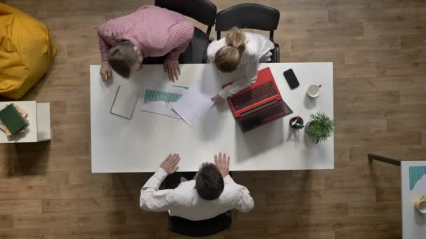 Team of three young business people coming in and discussing project, topshot, sitting at table in modern office