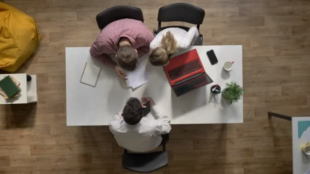 Team of three young business people going away and discussing project, topshot, sitting at table in modern office