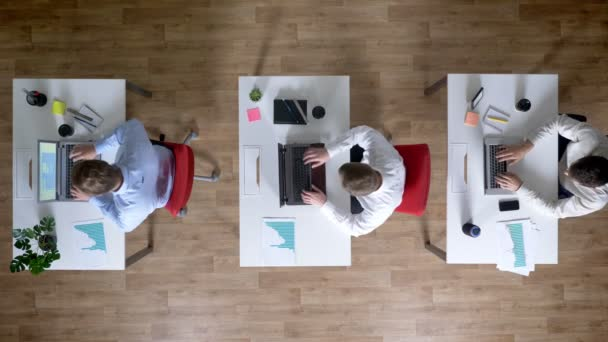 Három fiatal üzletember van működő-ra laptops, ital kávé egyszerre, működik a koncepció, a Hivatal koncepció, a kommunikáció fogalma, top shot