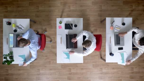 Három fiatal üzletember dolgozik-ra laptops, nézni a diagramok egyszerre, működik a koncepció, a Hivatal koncepció, a kommunikáció fogalma, a top shot