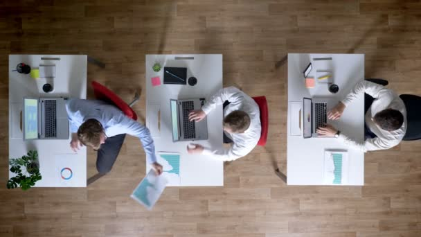 Three young businessman are working on laptops, pass diagrams, work concept, office concept, communication concept, top shot