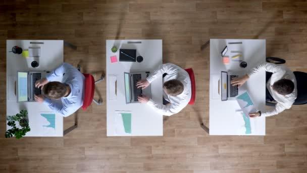 Három fiatal üzletember van működő-ra laptops, át, és nézni a diagramok, működik a koncepció, a Hivatal koncepció, a kommunikáció fogalma, top shot