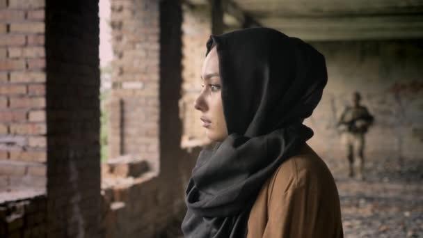 Junge traurig Muslima Hijab ansehen, Soldat mit Munition kommend in Richtung Frau, verlassene Gebäude Hintergrund, Terrorismus