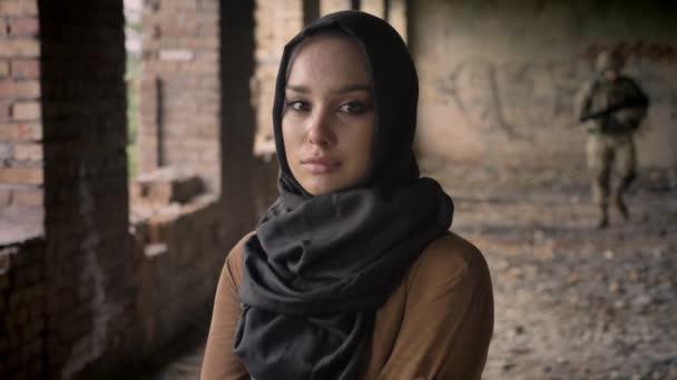 Junge traurig Muslima Hijab, Soldat mit Waffe und Munition, die im Hintergrund laufen aufgegeben Gebäudekonzept, Militär, Krieg