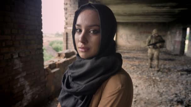 Junge muslimische Frau Hijab Weinen und Blick in die Kamera, Soldat mit Gewehr laufen im Hintergrund, verlassenen Gebäude, Terrorismus-Konzept