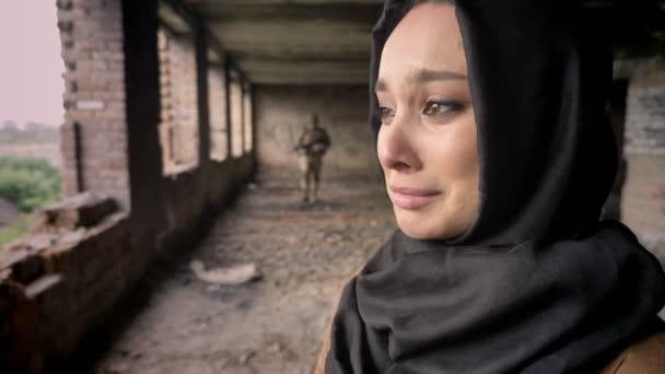junge traurige muslimische Frau im Hidschab weint, als bewaffneter Soldat auf Frau zugeht, verlassenes Gebäude, Kriegskonzept