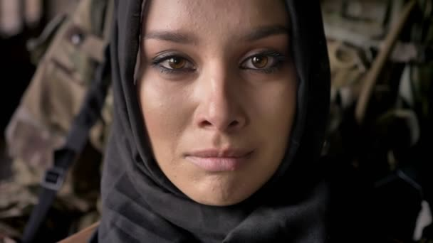 Close portrait of young muslim woman in hijab crying and looking at camera, armed soldier with weapon standing behind woman, war
