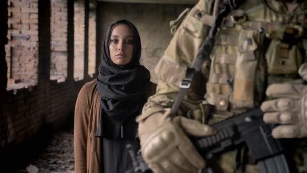 Junge muslimische Frau Hijab stehend hinter bewaffneter Soldat mit Waffe und Blick in die Kamera mit traurigen Blick, Krieg-Konzept