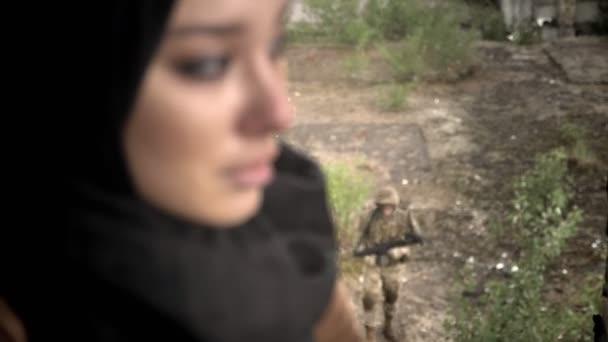 Junge traurig Muslima Hijab drehen und Blick in die Kamera, bewaffnete Mann mit Waffe gehen im Freien, Regentag, Terrorismus-Konzept