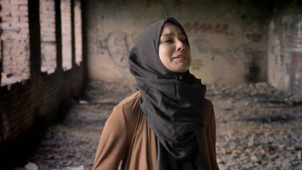 junge muslimische Frau im Hidschab schreit bewaffneten Soldaten an, steht in verlassenem Gebäude, Terrorkonzept