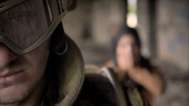 Bewaffnete Soldaten, Blick in die Kamera als Muslima Hijab schreien und Weinen hinter Mann aufgegeben Gebäude Hintergrund, terroristische Konzept