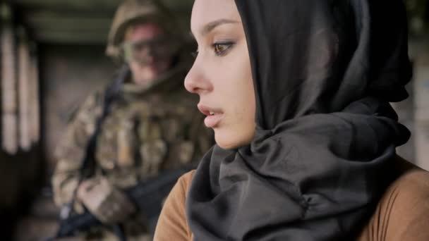 Junge muslimische Frau Hijab drehen und auf der Suche nach Soldaten hinter ihr Blick in die Kamera mit Angst und Schrecken Ausdruck, Krieg-Konzept