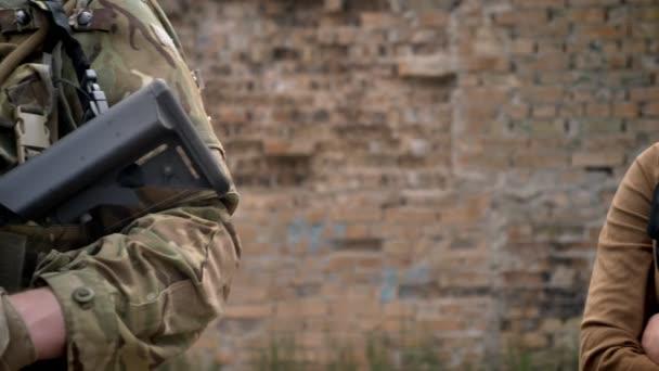 Junge schöne Muslima Hijab Soldat mit Waffe, stehen in der Nähe von Ziegel Wand Hintergrund, den Terrorismus Konzept zu betrachten