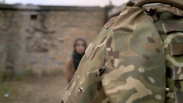 Bewaffnete Soldaten zu Fuß in der Nähe stehende Muslima Hijab, Frau Kamera, bewegliche Kamera, verfallenen Backsteingebäude Hintergrund betrachten