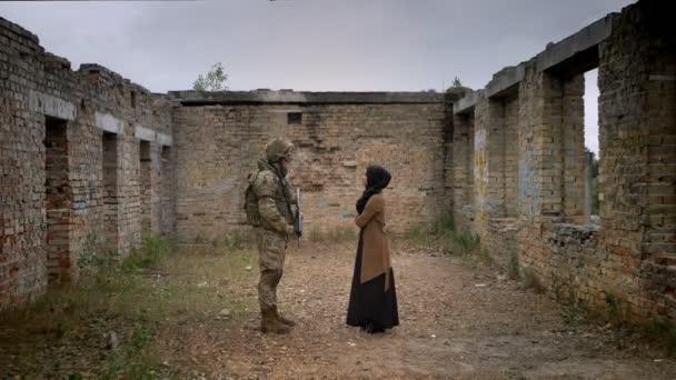 Bewaffnete Soldaten und junge Muslima Hijab in zerstörten gemauerten Gebäude und sahen einander, Krieg-Konzept