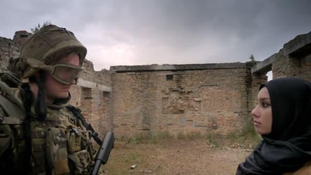 Jungen kaukasischen Soldaten und Muslimin in Hijab stehen in Backstein ruiniert Gebäude und sahen einander, Krieg-Konzept