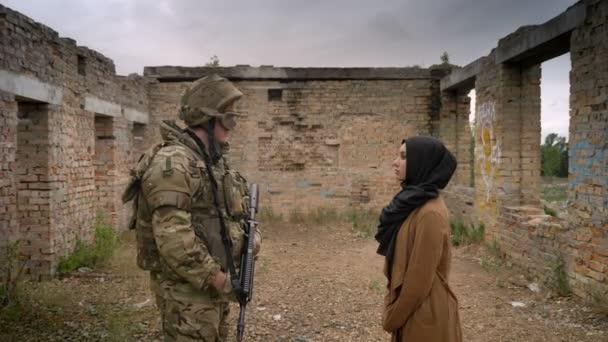 Junge muslimische Frau Hijab bewaffneter Soldat mit Waffe und stehend innen ruiniert Ziegelhaus