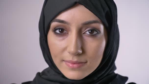 Muslimská dívka v hidžábu otevře oči a hodinky za kameru, sní koncept, šedé pozadí