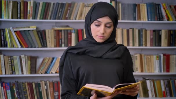 Young serious muslim girl in hijab is reading book, watching at camera, religious concept, bookshelf on background