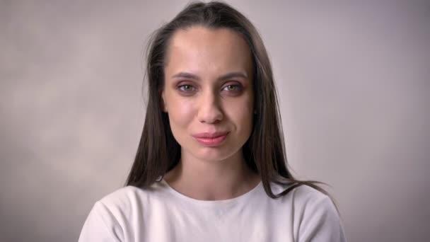 Mladá brunetka se dívá na fotoaparát, s úsměvem, šedé pozadí