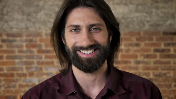Young nice brunette man with beard is watching at camera, smiling, brick background