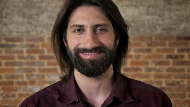 Young handsome brunette man with beard is watching at camera, smiling, brick background