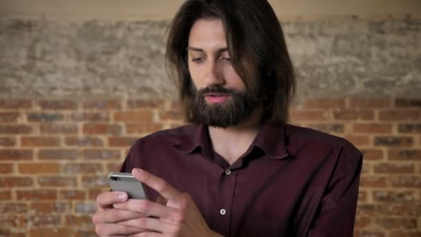 Young attractive brunette man with beard is watching in smartphone, watching at camera, brick background, communication concept