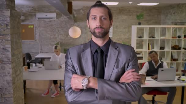 Hezký přesvědčeni, že stojí podnikatel s bradkou a s rukama překročili a sledování na kameru v úřadu, kolegové pracují s notebooky, pracovní koncept