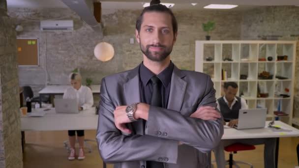 Pohledný podnikatel s vousy stojí s rukama zkříženýma a sledování na kameru v úřadu, s úsměvem, kolegové pracují s notebooky, pracovní koncept