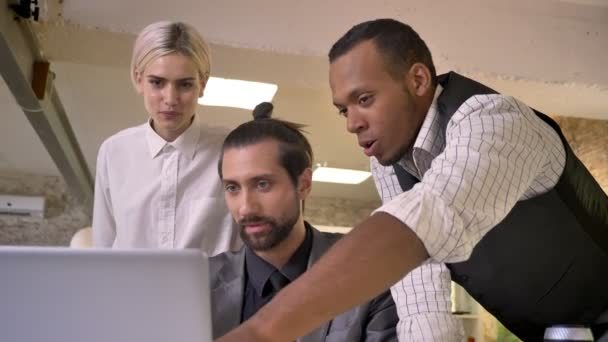 Three multy-ethnic workers discuss idea on laptop, coworking concept, communication concept