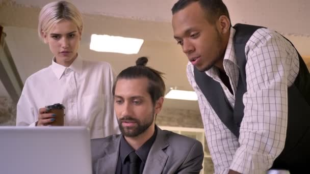 Three multy-ethnic workers discuss idea on laptop in office, coworking concept, communication concept