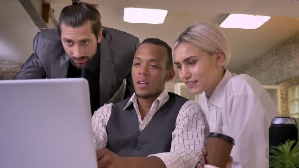 Three multy-ethnic workers discuss idea on laptop, laughing, coworking concept, communication concept