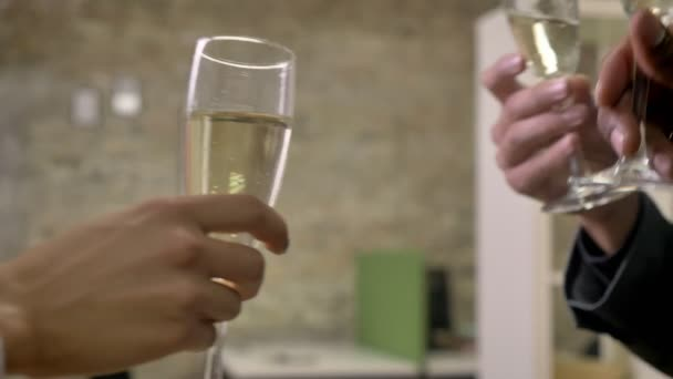 Three hands of business workers clink glasses with champagne in office, company party concept