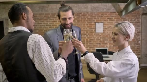 Three multy-ethnic workers dancing in office, clink glasses, drinking champagne, company party concept