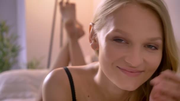 Mladá sexy blonda dáma leží na prádlo na pohovce, mává nohy, flirtovat koncept, relax koncept