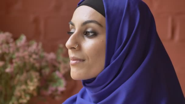 Young beautiful muslim woman in hijab turning and looking at camera, flowers and wall in background