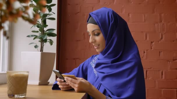 Young charming muslim woman in hijab rewrite info from card to her phone and smiling, sitting in cafe, beautiful female with pierced nose
