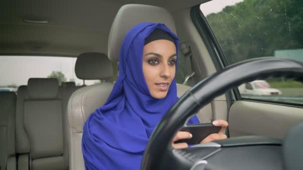 Mladá muslimka v hidžábu sedí za samořiditelná volant autonomní autopilota bez řidiče auta a psaní na mobilním telefonu