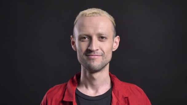 Inspirované blondýn bokovky se dívá na kameru, s úsměvem, černé pozadí