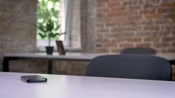 Az üres modern irodai asztalon fekvő mobiltelefon