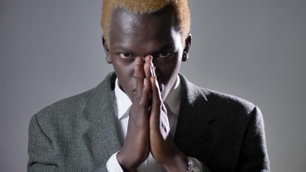 Young afro-american blond man in suit holding hands and praying, looking in camera, isolated on grey background