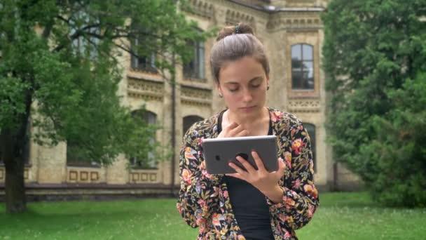 Mladí okouzlující vysokoškolský student procházení na tabletu a sedí v parku u univerzitní kampus, koncentrace a důvěra